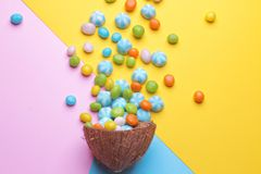 Colorful explosion of sweets in a coconut on bright multi-colored backgrounds, creative still life. Top view stock photography