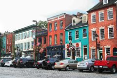 Historic buildings line cobblestone streets in Fells Point, Baltimore MD. Colorful exteriors beckon visitors to partake of the lively goings-on in the Fells stock photography