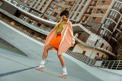 Colorful extraordinary chocolate woman widely stepping in pink shoes. Authentic woman bending. Colorful extraordinary chocolate woman widely stepping in pink stock images