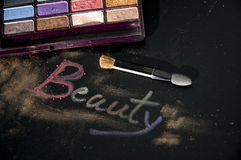 Colorful eyeshadow with words beauty. Colorful eyeshadow and brush with words beauty on black background Royalty Free Stock Image