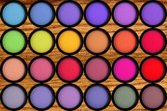 Colorful eyeshadows in black boxes on the wooden Royalty Free Stock Photos