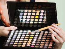 Colorful eyeshadows palette, makeup brush in female hand Royalty Free Stock Image