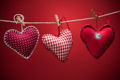 Colorful fabric hearts on red backgrounds Royalty Free Stock Photo