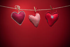Colorful fabric hearts on red backgrounds Stock Photography