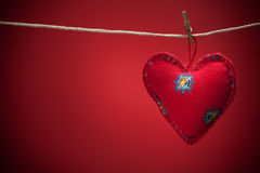 Colorful fabric hearts on red backgrounds Stock Images