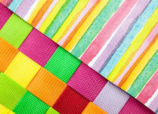 Colorful fabric and paper. Colorful striped paper with woven square fabric  close up Royalty Free Stock Image