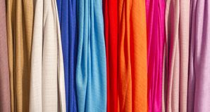 Colorful fabric texture silk scarves background. Row of colourful silk scarves hanging at a market .Colorful fabric background, pink gold and blue color silk Royalty Free Stock Image