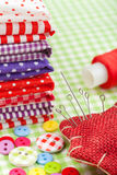 Colorful fabrics, buttons, pin cushion, thimble, spool of thread - set for sewing Stock Images