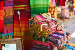 Colorful fabrics and carpets for sale on a street in Medina Royalty Free Stock Photo