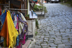 Colorful Fabrics in an Old Cobblestone Street Royalty Free Stock Photos