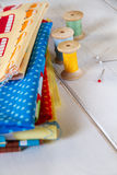 Colorful fabrics with pins, measuring tape and rolling cotton Stock Photos