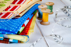 Colorful fabrics with pins, measuring tape and rolling cotton threads Royalty Free Stock Photography