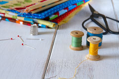 Colorful fabrics with vintage scissors, pins, measuring tape and rolling cotton threads Royalty Free Stock Photo