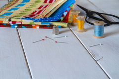 Colorful fabrics with vintage scissors, pins, measuring tape and rolling cotton threads Stock Photos