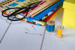 Colorful fabrics with vintage scissors, pins, measuring tape and rolling cotton threads on white wooden table Stock Photo
