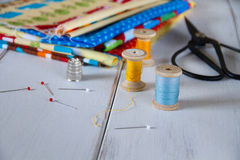 Colorful fabrics with vintage scissors, pins, measuring tape and rolling cotton threads Royalty Free Stock Image