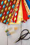Colorful fabrics with vintage scissors, pins, measuring tape and rolling cotton threads on white wooden table Stock Photos