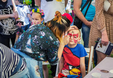 Colorful face painting for a boy. Zaporizhia/Ukraine- June 5, 2016: volunteer  painting mask on a boy`s face during charity family festival organized in regions Stock Photos