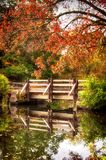 Colorful Fall Foliage at Southford falls. A wooden bridge crossing water with the colorful fall foliage of autumn in New England reflecting off of the waters at royalty free stock images