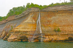 Colorful Falls on a Lakeshore Cliff Stock Photo