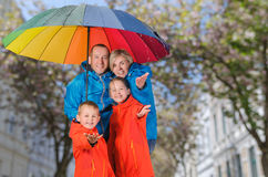 Colorful family have fun under rain. Colorful family, mother, father, son and daughter, have fun under rain Royalty Free Stock Photography