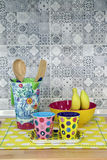 Colorful fancy cup and fancy utensil on yellow polka dot napery Royalty Free Stock Photography