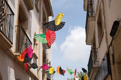 Colorful fans strung above narrow street Royalty Free Stock Image