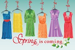 Colorful fashion cocktail dress hang on ribbon. Royalty Free Stock Photo