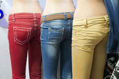 Colorful Fashion Jeans in Store Display. Colorful fashion jeans in a store display. The pants have the bright colors of red, blue, and yellow Stock Photo