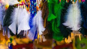 Colorful feathers in the form of a border. With white, green and black color stock images