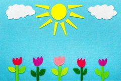 Colorful felt background with sun, clouds and tulip flowers,. Copy space Royalty Free Stock Photography