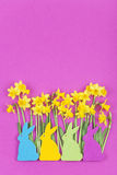 Colorful felt Easter bunnies in front of daffodils Stock Image