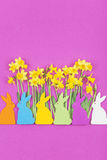 Colorful felt Easter bunnies in front of daffodils Royalty Free Stock Images