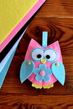 Colorful felt owl toy. Handmade childrens crafts. Felt sheets, sewn toy owl on a wooden table. Close-up Stock Photos