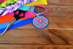 Colorful felt pendant - handmade jewelry. Scissors, sheets of felt on a wooden background with copy space for text Stock Image