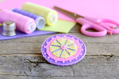 Colorful felt round flower decorated with pink beads. Handmade felt flower, scissors, thread, colorful felt sheets, thimble Stock Image