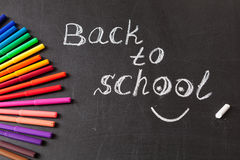 Colorful felt tip pens and title Back to school written by  chalk on the black school chalkboard Stock Photo