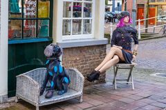 Colorful female and dog lay figures sitting on corner of a  street royalty free stock photos