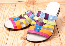 Colorful female low-heeled sandals on a light wooden background Stock Photography