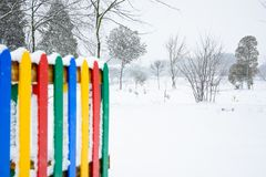 Colorful fence in snowy park stock image