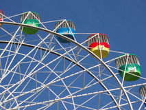 Colorful ferris wheel. Side view of colorful ferris wheel with blue sky background Royalty Free Stock Photo