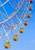 Colorful ferris wheel on blue sky background. Colorful ferris wheel with vivid baskets on blue sky background (nobody&#x29 Stock Photo