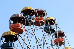 Colorful ferris wheel slowly moving against blue sky in the amusement park Stock Images