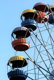 Colorful ferris wheel slowly moving against blue sky in the amusement park Royalty Free Stock Photography