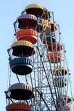 Colorful ferris wheel slowly moving against blue sky in the amusement park Stock Photos