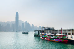 Colorful ferry boat and the Hong Kong skyline in the background. Stock Photos