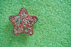 Colorful fertilizer in red star shape on green magnesium fertilizer background. Stock Photos