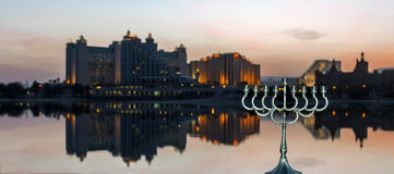 Colorful festive card with city of Eilat and menorah on foreground Stock Photos