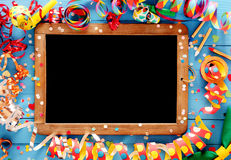 Colorful festive frame around a vintage slate. Colorful festive frame with multicolored coiled party streamers on a blue wooden background around a vintage slate Stock Photo