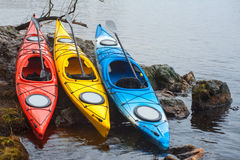 Colorful fiberglass kayaks lying on the rocky shore01 Stock Photography